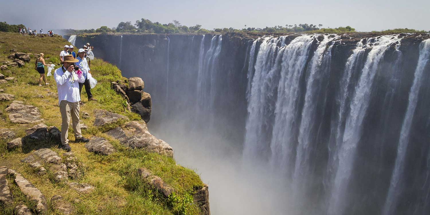 tourists take photos next to Victoria Falls