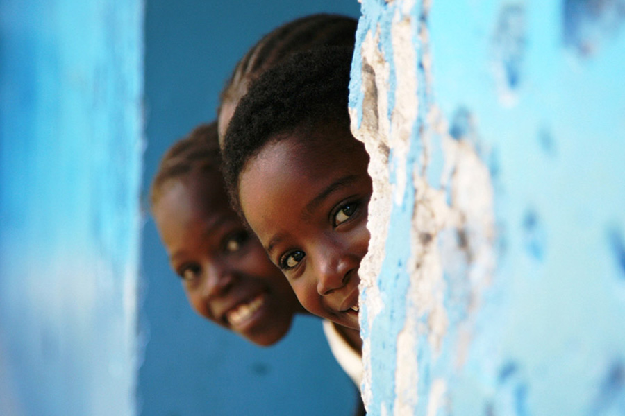 three young children peek head out of wall for photo