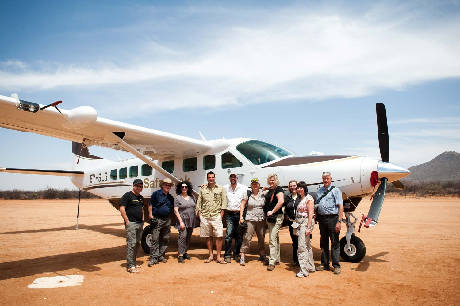 ten travellers in front of plane for safari