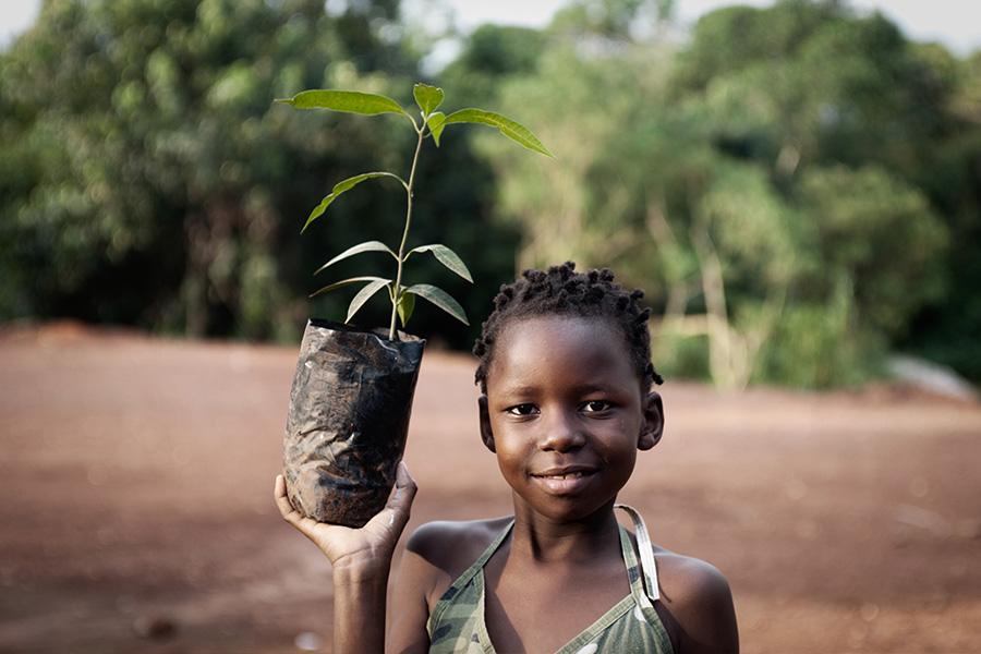 young child holding up plant ready to grow